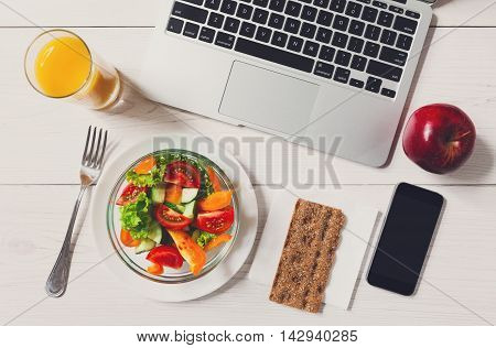 Healthy business lunch in the office, top view of vegetable salad on white wooden desk near laptop computer keyboard. Salad bowl, juice, mobile phone and apple flat lay. Snack at break time