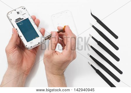 Smartphone disassembling with special tools. Phone repair service, male hand removing plastic case from communication device, white background with disassembling instruments