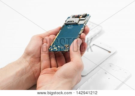 Smartphone dismantling on white background. Repairman hands holding telephone in hands. Disassembled phone in repair service, white background, electronics recovery concept