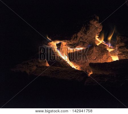 Night campfire fenced with brick billets burning