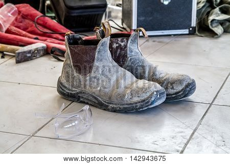 Dirty worker boots and construction tools on the floor of ceramic tiles