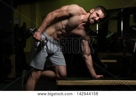 Young Man With Dumbbell Exercising Triceps