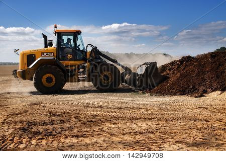 KALKHORST GERMANY AUGUST 16 2016: Excavator with shovel working on a steaming mountain of manure organic fertilizer for the field blue sky copy space
