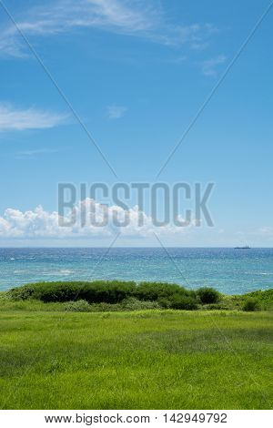 Beautiful tropic ocean and sky seen from grassy green hill. Early summer ocean with clear blue coral reef water.