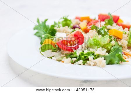 Homemade autumn healthy salad with quinoa salad leaves tomatoes pumpkin and feta cheese on a white plate closeup selective focus
