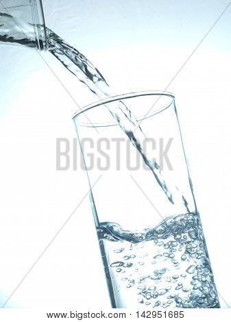 Pouring fresh table water toned in blue healthy food concept