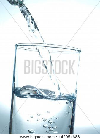 Pouring fresh table water in a glass blue toned healthy concept image