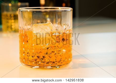 Whiskey With Ice Cubes In Glass With Bottle In Background
