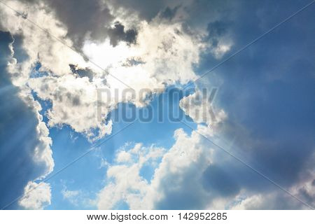 The sun is hidden behind clouds. Sun rays through the clouds.