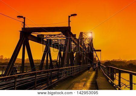 Hanoi, Vietnam - 18 November,2012: People go home in the sunset at Long Bien bridge