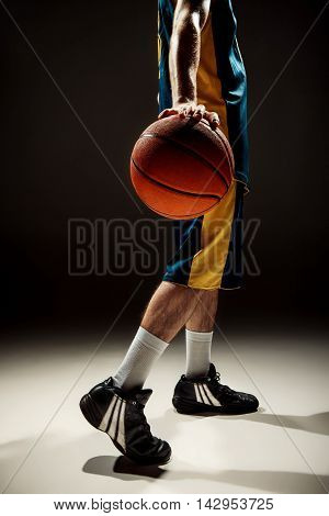 The silhouette side view of a basketball player holding basket ball on black background