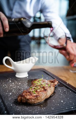 New York steak with waiter pouring red wine on background
