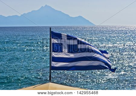 Greek flag on a sailing ship with holy mountain Athos in background, Greece