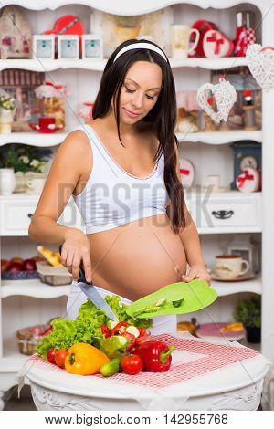 Pregnant woman in the kitchen preparing a vegetable salad. Healthy nutritious. Last months of pregnancy.