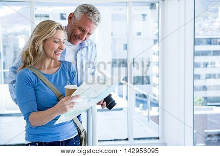 Happy mature couple reading map at home