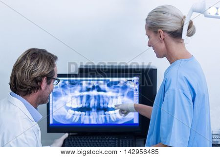 Dentist and dental assistant discussing a x-ray on the monitor in dental clinic