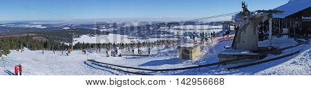Winter sports area on the Fichtelberg in the Ore Mountains in Saxony, Germany, winter sportsmen, snow-capped landscape, blue sky over the clouds, panoramic,