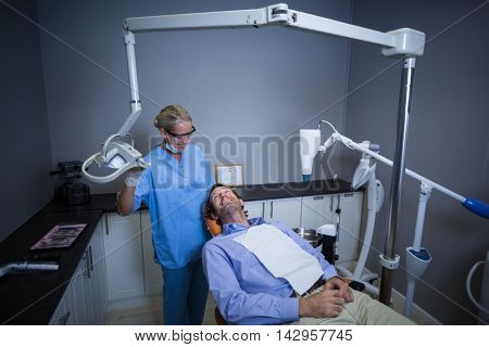 Smiling dentist assistant adjusting light over patients mouth at the dental clinic