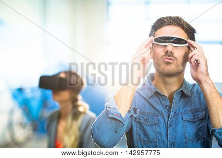 Young man using the virtual reality video glass in office