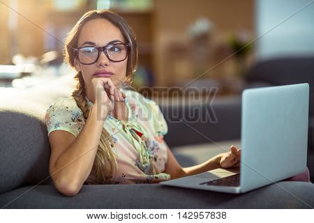Thoughtful woman sitting on sofa and using laptop in office