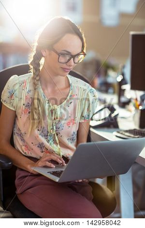 Woman sitting on chair and using laptop in office