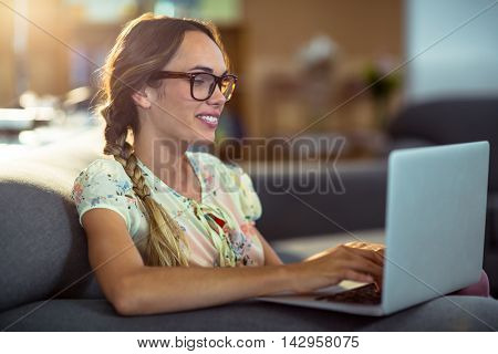 Smiling woman sitting on chair and using laptop in office