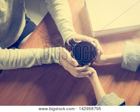 Hands of mother and daughter holding coffee cup on wooden table under shinning light