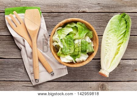 Fresh healthy romaine lettuce salad on wooden table. Top view