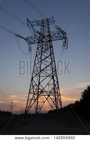 The silhouette of the evening electricity transmission pylon.