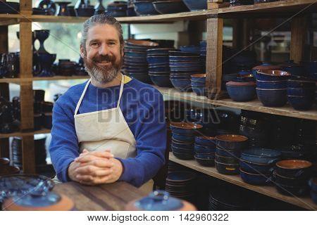 Portrait of male potter smiling at pottery workshop