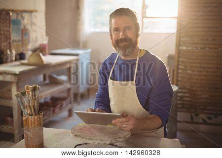 Portrait of male potter using digital tablet in pottery workshop