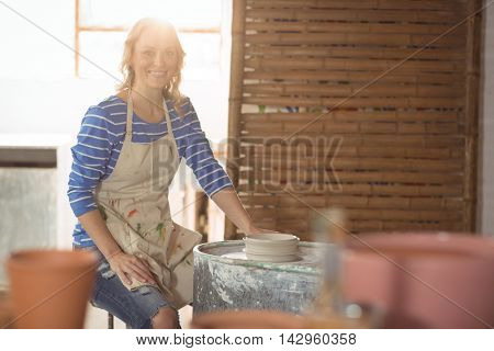 Beautiful female potter making pot in pottery workshop