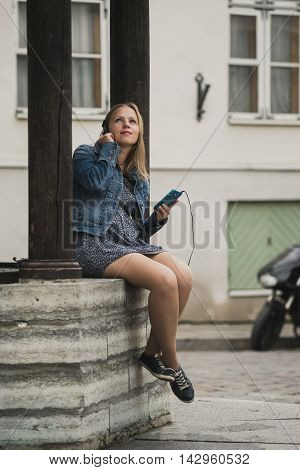 Young positive woman with smartphone and headphones listening to music in the city