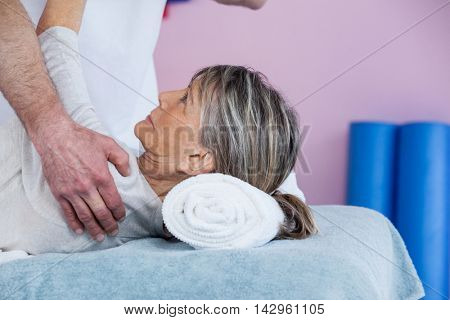 Physiotherapist massaging a senior womans shoulder in clinic