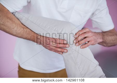 Mid section of physiotherapist giving leg massage to a patient in clinic