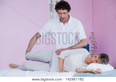 Physiotherapist massaging a senior womans leg in clinic