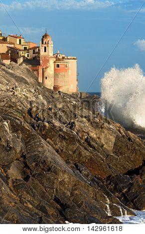 Detail of Tellaro village with the Church of St. George (San Giorgio) with cliffs and white sea wave. La Spezia Liguria Italy