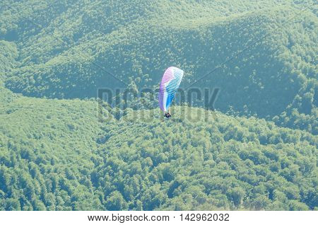 Paraglider In The Sky Over The Green Hills