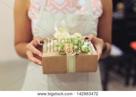 Woman's hands hold decorated gift box wrapped in kraft paper and decorated with flowers