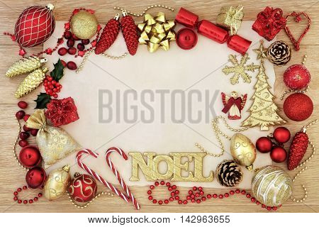 Christmas abstract background border with gold noel sign, tree decorations and baubles with holly on parchment paper over oak wood.