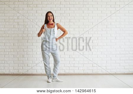 Smiling beautiful woman wear strip overalls, standing and trying on fancy butterfly, white brick wall on background