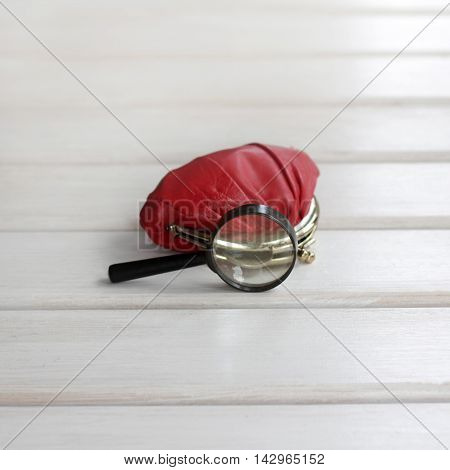 background with red purse and looking out his coin under a magnifying glass / small monetary savings