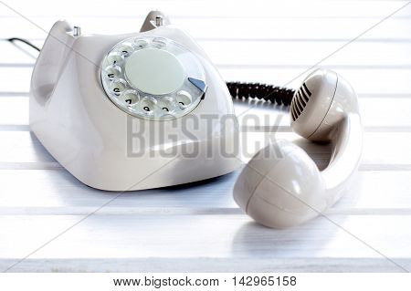 dial analog telephone and lying next the telephone receiver lying on a light wooden table / subscriber not available