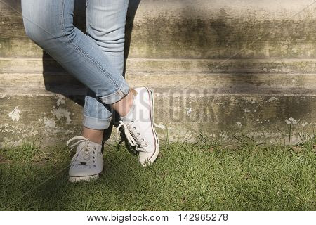 crossed female legs wearing a white sneakers standing on a patch of grass