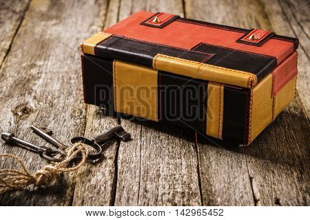 Leather box. Multicolored blocks leather box on a rustic wooden background with old keys. Vintage style. Selective focus