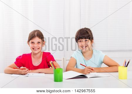 Cute little girls are enjoy drawing and writing together.