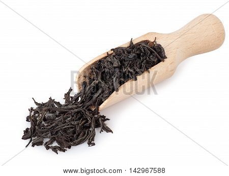 Black tea in wooden scoop isolated on white background. Black tea. Dry leaves of tea in spoon isolated on white