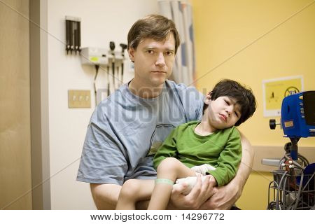 Worried father holding his sick son in hospital