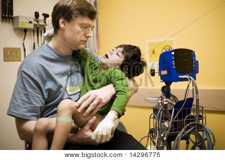 Worried father holding his sick disabled son