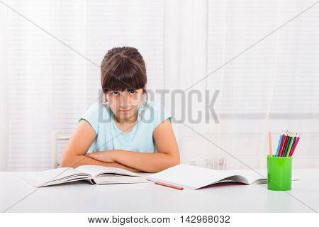 Angry little girl must stay at home and do her homework,but she would rather play outside.
